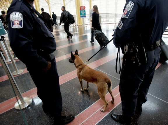 A K-9 police unit keeps watch as passengers make their way through Ronald Reagan Washington National Airport, photo by Kevin Lamarque/Reuters