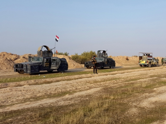 Iraqi security forces guard during the building of a new road between Diyala province and Samarra December 21, 2014. The Badr Organization, a leading political party and militia with ties to Iran, is supervising the new road, photo by Stringer/Reuters