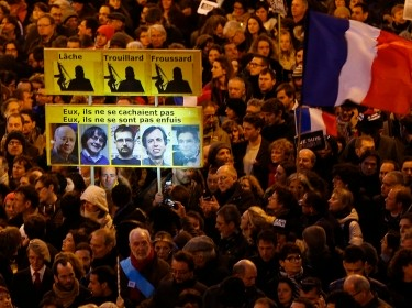 A Paris crowd displaying the portraits of five of the people killed during the attack at Charlie Hebdo on January 7, 2015