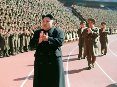 North Korean leader Kim Jong-un claps during a photo session at a meeting of military and political cadres in this undated photo released by the KCNA, February 2, 2015