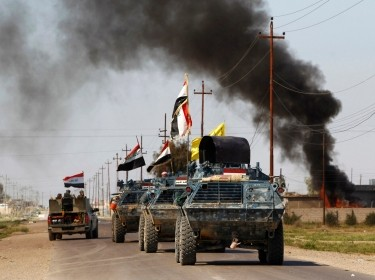 Armored vehicles of Iraqi security forces with militias known as Hashid Shaabi passing smoke arising from a clash with Islamic State militants in the town of al-Alam, March 10, 2015