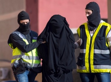 Spanish police arresting a woman suspected of recruiting women to go to Syria and Iraq to support Islamic State insurgents