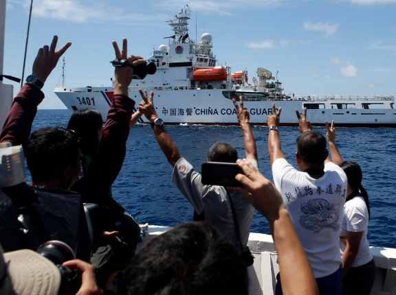 A Chinese Coast Guard vessel in the South China Sea maneuvers to block a Philippine supply ship with members of the media aboard, March 29, 2014, photo by Erik De Castro/Reuters