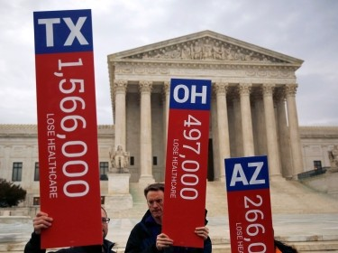 Demonstrators hold signs showing the number of people they say could lose affordable health care in King v. Burwell, in front of the Supreme Court building, March 4, 2015