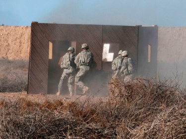 U.S. soldiers rush a building during a platoon live-fire demonstration for Iraqi army trainees and officers on Camp Taji, Iraq, Feb. 5, 2015