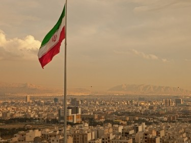 Iran flag above Tehran skyline