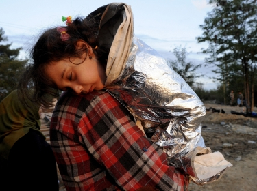 A Syrian refugee carries his sleeping daughter as they walk toward Greece's border with Macedonia, September 14, 2015