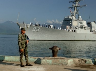 An Armed Forces of the Philippines marine sentry stands watch as the guided-missile destroyer USS Chung-Hoon arrives in Puerto Princesa to participate in Cooperation Afloat Readiness and Training