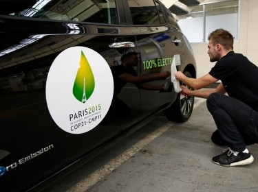 A man applies a sticker which reads 100% electric next to the logo of the upcoming COP21 Climate Change Conference on a Nissan LEAF electric car in Boulogne-Billancourt, France, November 16, 2015