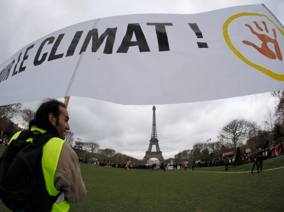 "Environmentalists hold a banner which reads in part, ""For the Climate,"" near the Eiffel Tower during the World Climate Change Conference 2015, photo by Mal Langsdon/Reuters"