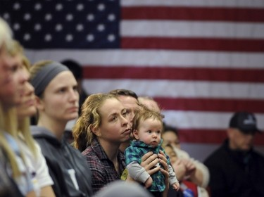 Elissa Wenthe (C) holds her 4-month-old son as she listens to U.S. Democratic presidential candidate Bernie Sanders speak at Upper Iowa University in Fayette, Iowa, January 24, 2016