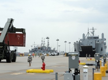 Transportation soldiers and civilian harbormasters move cargo containers onto awaiting vessels in a training exercise at Joint Base Langley-Eustis