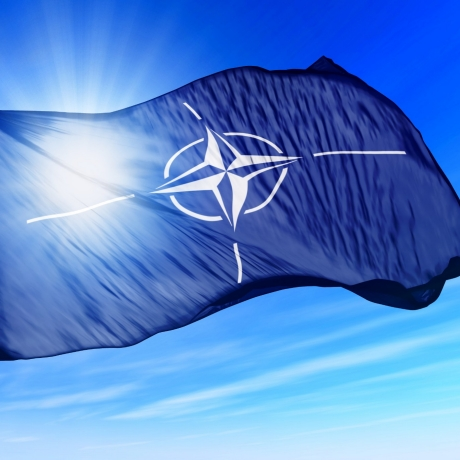 The NATO flag flies on a sunny day, photo by Lulla/Fotolia