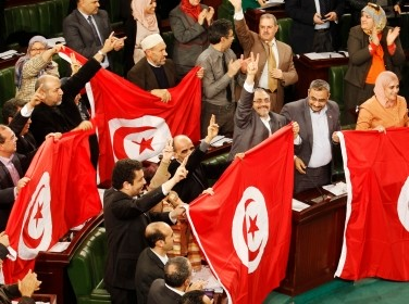 Members of the Tunisian parliament wave flags after approving the country's new constitution in Tunis, January 26, 2014