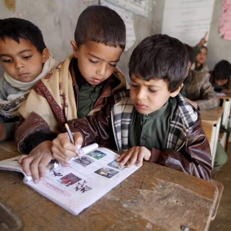 Boys study with a shared book at their school in a village outside Sanaa, Yemen, February 2, 2016, photo by Khaled Abdullah/Reuters