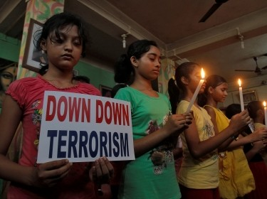 Students hold a placard and candles during a vigil after a terror attack on Dhaka, Bangladesh, in Agartala, India, July 3, 2016