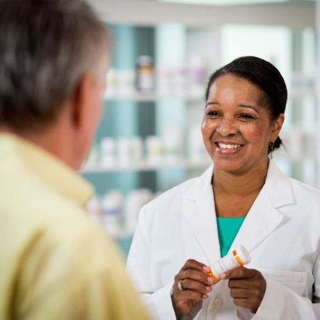 Pharmacist discussing a prescription with a patient, photo by stevecoleimages/Getty Images