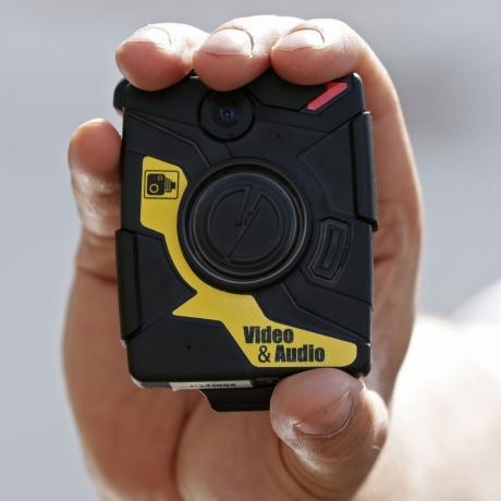Police Constable Yasa Amerat poses for a photograph with a body-worn video (BWV) camera, before a year-long trial by the Metropolitan police, at Kentish Town in London, May 6, 2014, photo by Yui Mok/Reuters