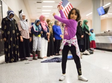 A girl dances while women pray at a protest against the Trump administration's travel restriction at Dallas/Fort Worth International Airport, Texas, January 29, 2017