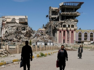 People walk in front of the remains of the University of Mosul, which was burned and destroyed during a battle with Islamic State militants, in Mosul, Iraq, April 10, 2017.