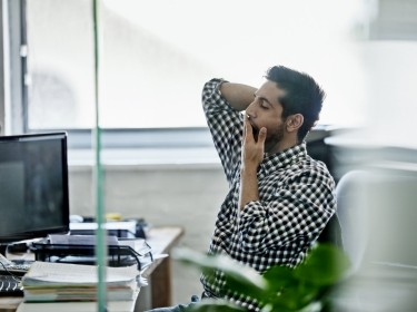 Man yawning at a desk in an office