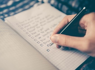 A person's hand writing a checklist