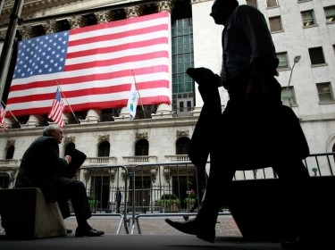 Morning commuters are seen outside the New York Stock Exchange, July 30, 2012