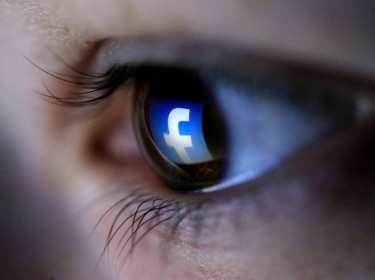 The Facebook logo is reflected in a person's eye, March 13, 2015
