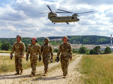 Soldiers walk to their fuel trucks after refueling a CH-47 Chinook helicopter at a forward area refueling point during a readiness training exercise at Hohenfels Training Area, Germany, July 12, 2018.