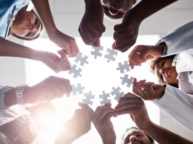 Group of hands holding puzzle pieces in a circle