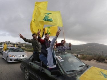 Supporters of Lebanon's Hezbollah leader Sayyed Hassan Nasrallah gesture as they hold Hezbollah flags in Marjayoun, Lebanon, May 7, 2018