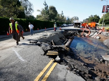 Department of Water and Power employees assess the damage from a broken 30-inch water main on Sunset Boulevard, next to the UCLA campus in the Westwood section of Los Angeles, July 30, 2014, photo by Lucy Nicholson/Reuters