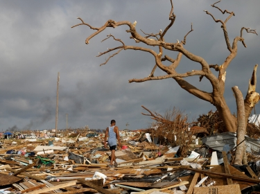 A man walks among debris at the Mudd neighborhood, devastated after Hurricane Dorian hit the Abaco Islands in Marsh Harbour, Bahamas, September 6, 2019, photo by Marco Bello/Reuters
