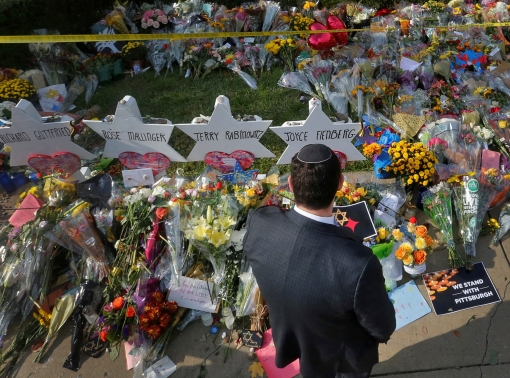 A man prays at a memorial outside the Tree of Life synagogue in Pittsburgh, Pennsylvania, following a mass shooting there four days earlier, October 31, 2018