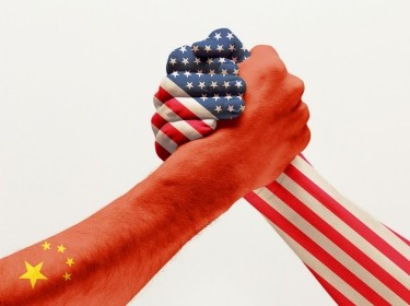 Two hands colored with flags of China and United States clasping, photo by master1305/Getty Images