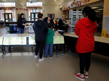 Children pick up lunch at the Olympic Hills Elementary School, after schools were closed due to the COVID-19 outbreak, in Seattle, Washington, March 17, 2020, photo by Brian Snyder/Reuters
