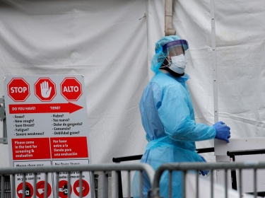 A health care worker in protective equipment enters the Brooklyn Hospital Center during the COVID-19 outbreak in Brooklyn, New York, March 31, 2020, photo by Brendan McDermid/Reuters