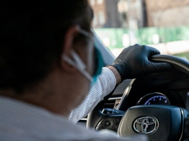 A rideshare driver wears gloves and a mask while driving following the outbreak of COVID-19, in New York City, March 15, 2020, photo by Jeenah Moon/Reuters