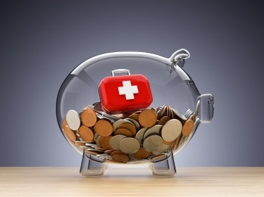 Clear piggy bank with coins and red medical case, photo by Altayb/Getty Images