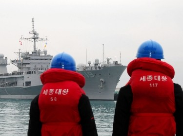 Two Korean sailors watch the U.S. 7th Fleet command ship USS Blue Ridge as it arrives in Busan, Republic of Korea, March 5, 2010, photo by Petty Officer 1st Class Bobbie Attaway/U.S. Navy