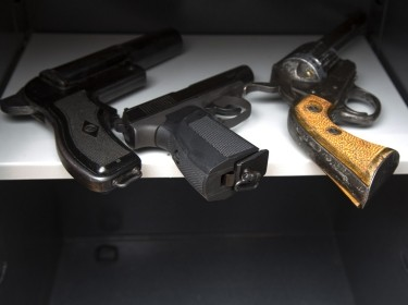 Three guns in an open safe, photo by SERGEI PRIMAKOV/Adobe Stock