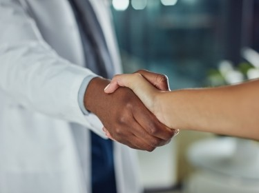 Closeup of hands of a Black doctor shaking hands with a white patient, photo by LumiNola/Getty Images