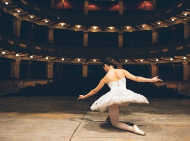 Ballet dancer on stage in an empty theater, photo by vgajic/Getty Images