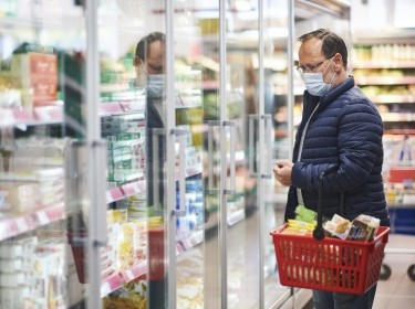Middle age man buying food in grocery store, wearing medical mask, photo by annanahabed/Adobe Stock