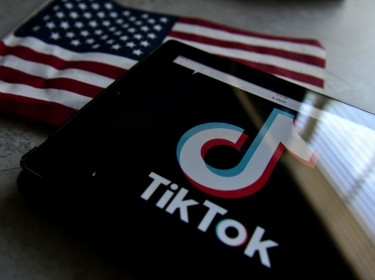 The logo of the social network application TikTok and a US flag shown on a mobile device screen in Miami, Florida, September 18, 2020, photo by Johnny Louis/Reuters