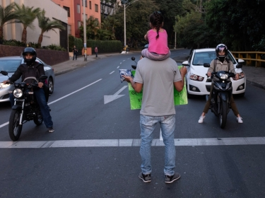 A Venezuelan refugee with his daughter on his shoulders asks for help at a traffic light in Medellin, Colombia, February 11, 2019, photo by David Himbert/Hans Lucas via Reuters Connect