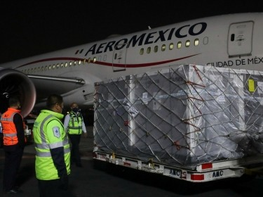 Workers stand near the first shipment of the AstraZeneca COVID-19 vaccine delivered under the COVAX scheme, at Benito Juarez's International Airport in Mexico City, Mexico, April 22, 2021, photo by Henry Romero/Reuters