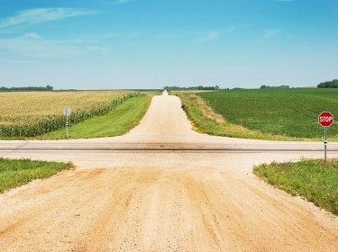 An intersection of gravel roads through a field