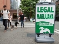 People passing a State Legal Marijuana shop sign on 2nd avenue late in the day in downtown Seattle, WA, July 14, 2016