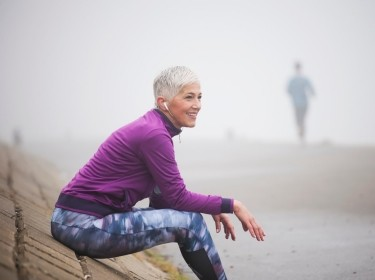 Older woman in athletic clothing resting on a sloping wall